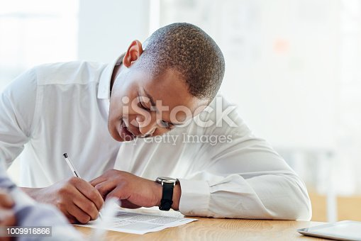 Shot of a young businessman filling in paperwork in an office
