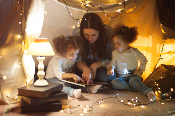 Reading and family games in children's tent stock photo