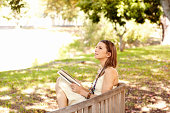 A beautiful woman sitting up against a tree and reading a book