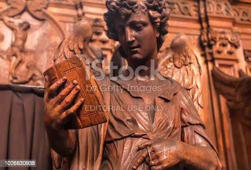 Antwerp, Belgium - March 30, 2018: Reading angel holding an old book, wooden statue in 17th century catholic church Saint Charles Borromeo on March 31, 2018. Near 1,200,000 people lives in Antwerp