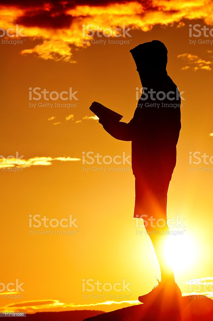 Reading Bible in the dramatic sunset - II royalty-free stock photo