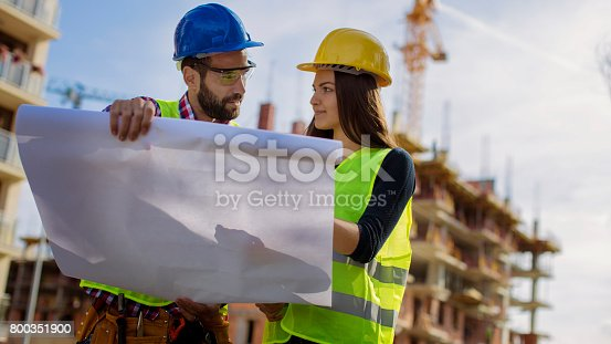617878058istockphoto Reading blue print at construction site 800351900