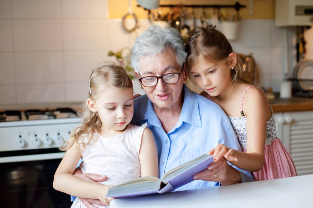 Reading book at home. Grandmother reads fairy tale. Kids listen to granny story in cozy kitchen. stock photo