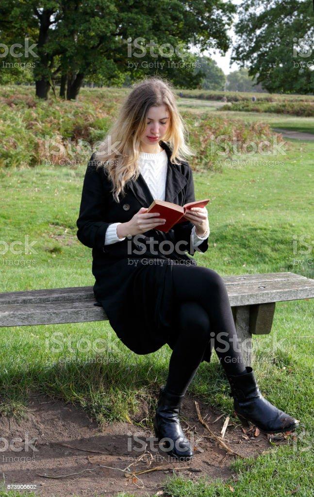 Reading book in open air blonde Bulgarian outdoor girl stock photo