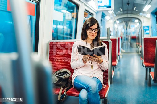Young woman is reading a book in subway train