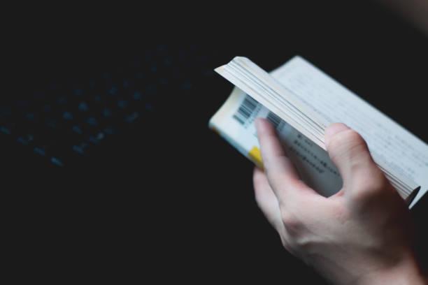 暗闇の中で本を読む ストックフォト