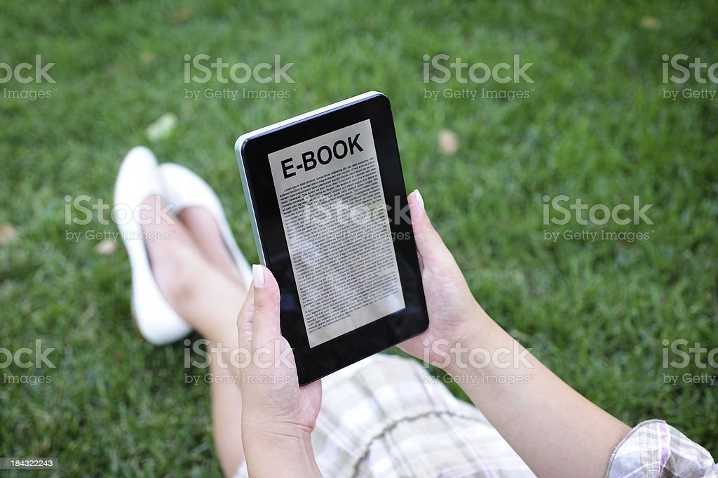 Reading E-book in park royalty-free stock photo