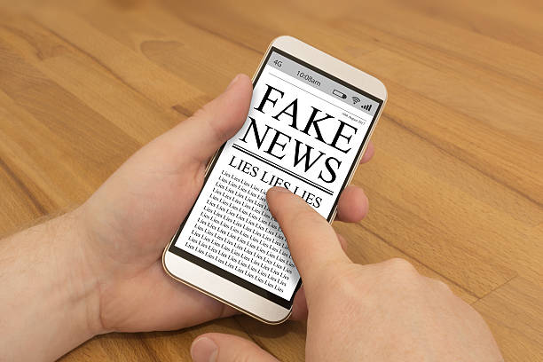 reading fake news on a smartphone - imitation stock photos and pictures