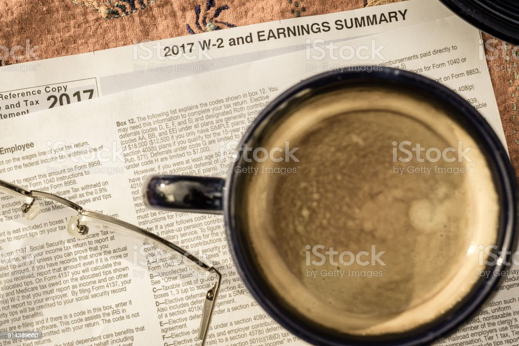 Reading glasses and cup of coffee resting on a statement of earnings (W-2) stock photo
