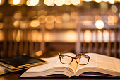 istock Reading glasses and digital tablet on book 497828764