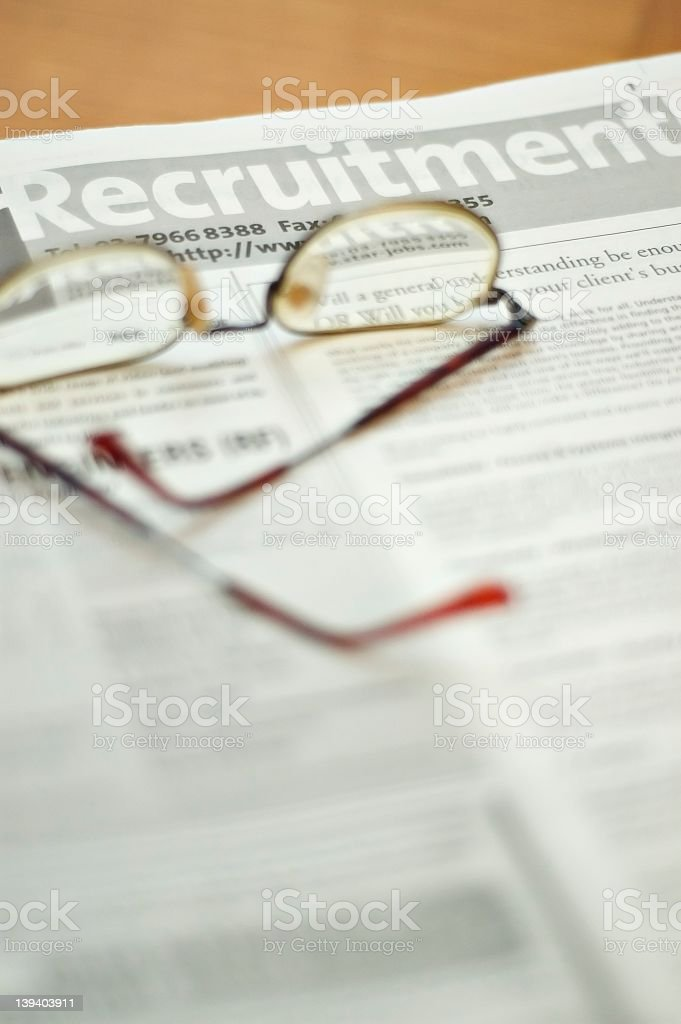 Reading glasses on a blurry newspaper stock photo