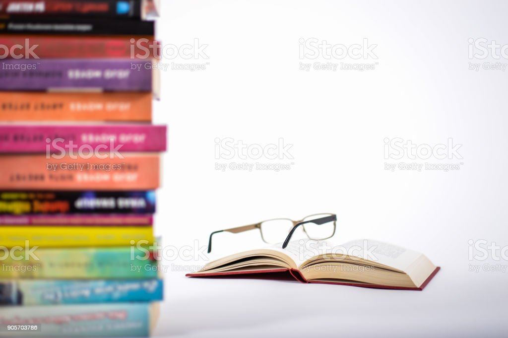 Reading glasses on top of a open book. stock photo
