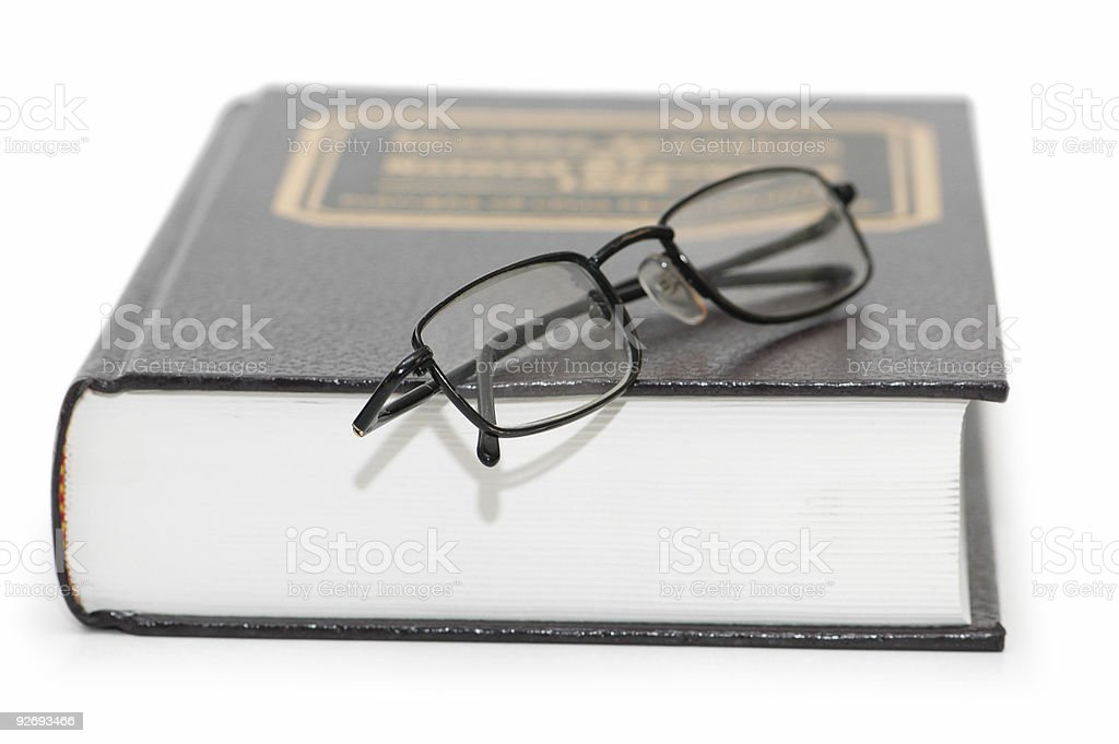 Reading glasses over the book isolated on white royalty-free stock photo