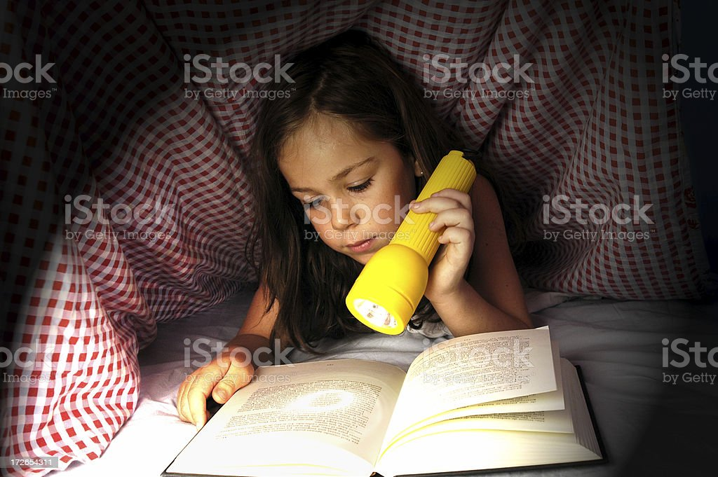 Reading hidden under covers royalty-free stock photo