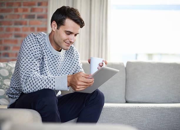 liest seine morning news-tablet - sofabezüge stock-fotos und bilder