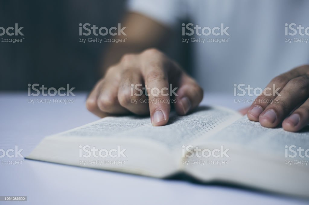 Reading Holy Bible Man is reading the holy bible. Adult Stock Photo