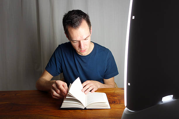 Reading in front of a seasonal affective disorder SAD lamp Handsome man reading in front of a seasonal affective disorder SAD lamp.  affective stock pictures, royalty-free photos & images