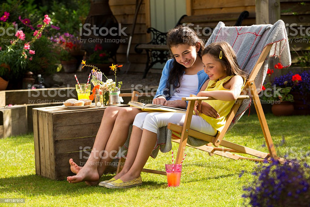 A shot of two happy sisters reading a book together on a sunny day....