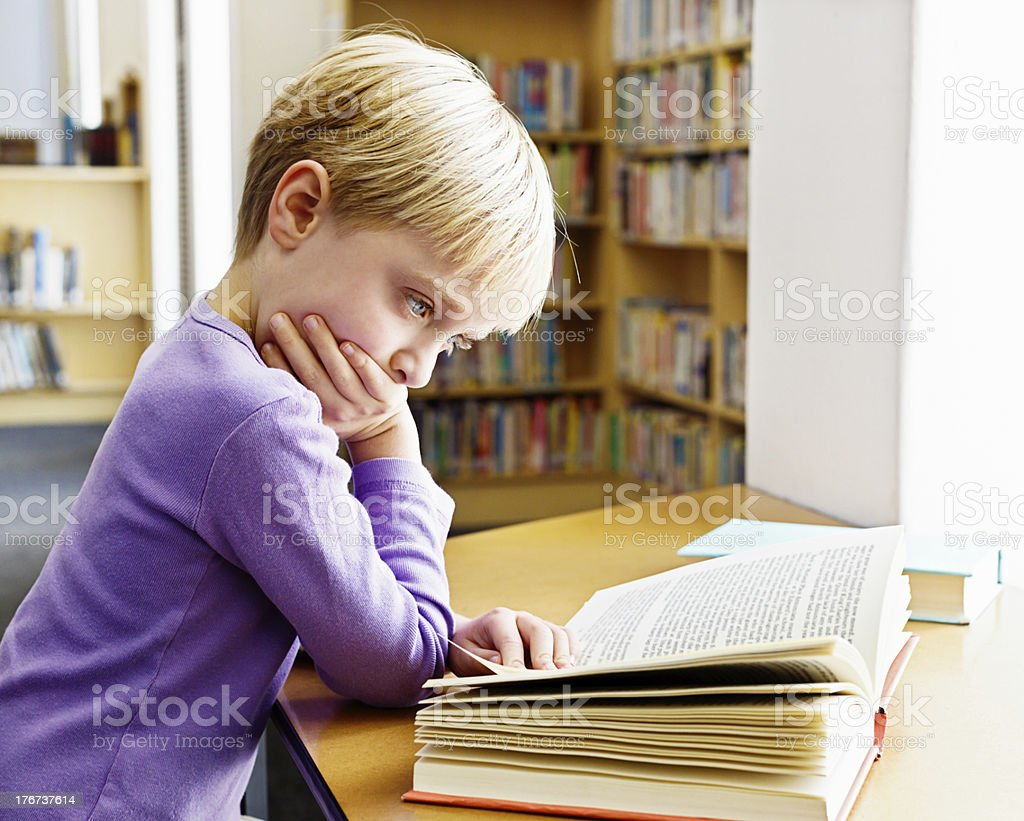 Reading is hard! Little girl in library concentrating on book royalty-free stock photo