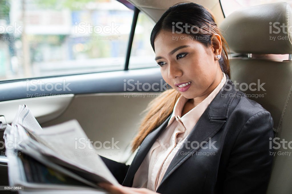 Reading latest news commuting to work on a taxi. stock photo