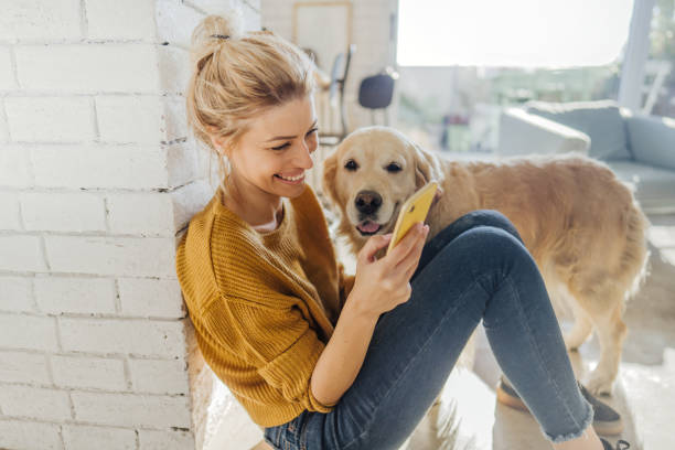 Reading morning news online with a company Photo of a young woman reading morning news online while her dog standing next to her lifestyles stock pictures, royalty-free photos & images