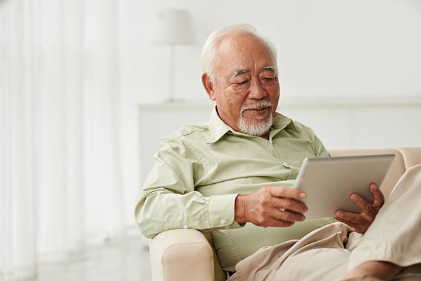 Reading news Senior Vietnamese man sitting on sofa and reading new on his tablet computer vietnamese ethnicity stock pictures, royalty-free photos & images