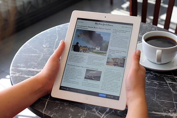lesen nachrichten mit ipad 3 - new york times stock-fotos und bilder