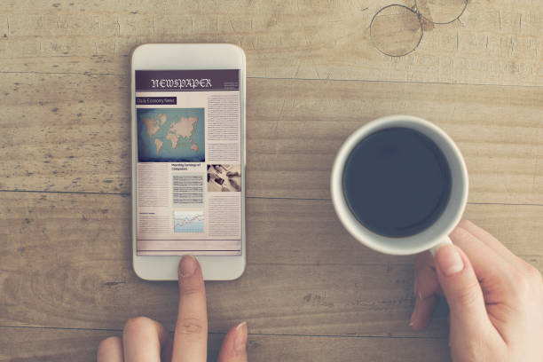 Reading newspaper from mobile phone holding coffee cup Reading newspaper from mobile phone holding coffee cup article stock pictures, royalty-free photos & images