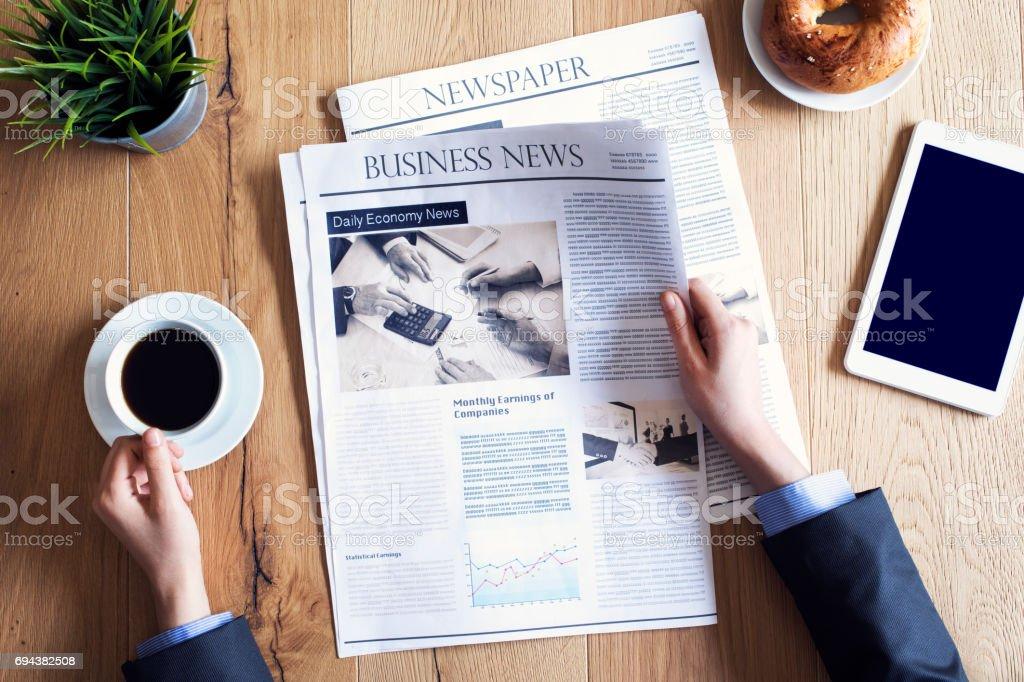 Reading newspaper on desk stock photo