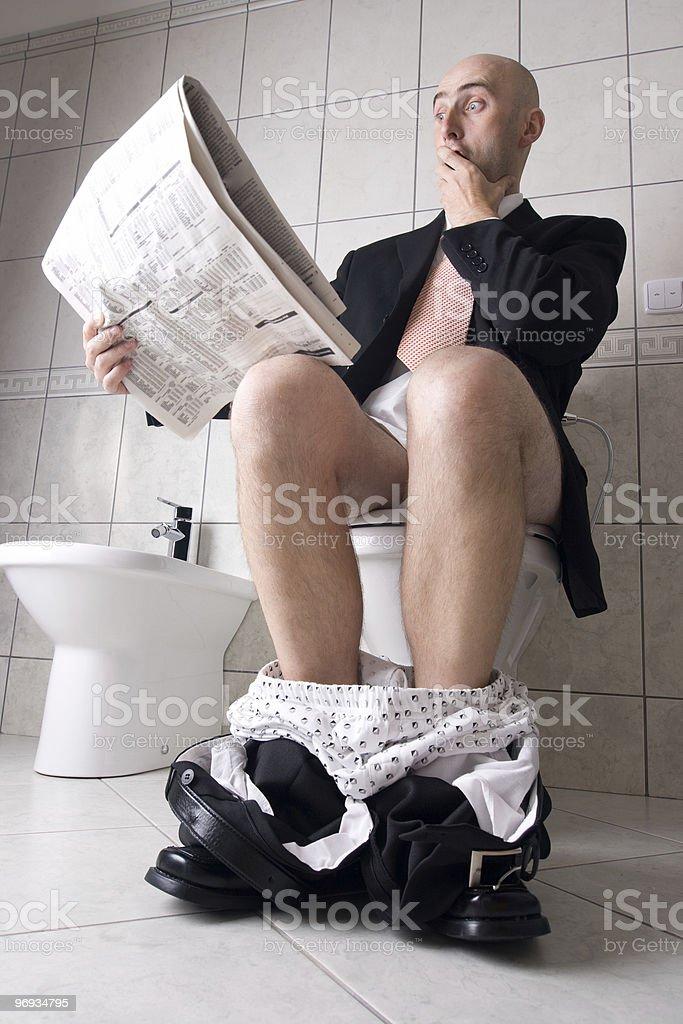 Reading newspaper on toilet royalty-free stock photo