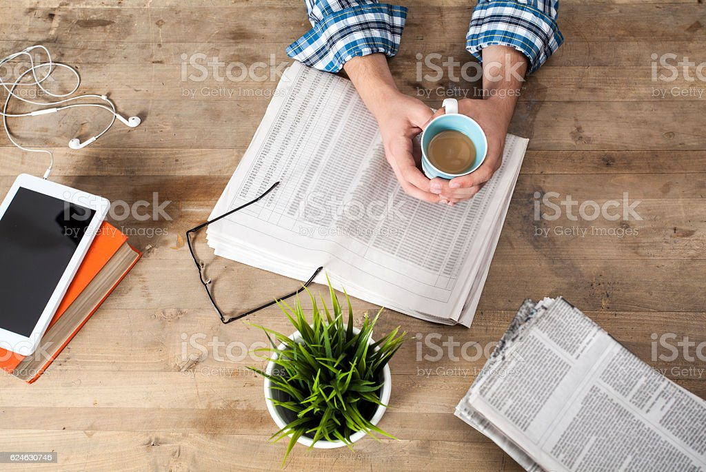 Reading newspaper on wooden table stock photo