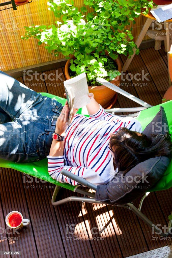 Läsa på en liten grön balkong - Royaltyfri Avkoppling Bildbanksbilder