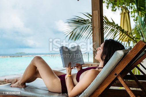 Young Caucasian attractive slim beautiful woman reading book by the sea on Maldives.