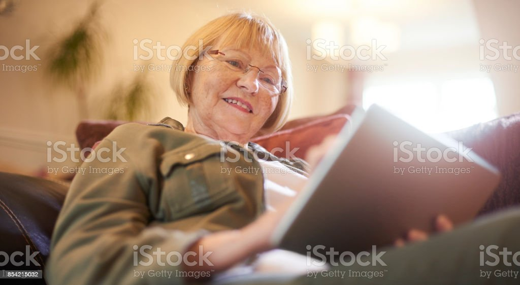 Reading on her digital tablet stock photo