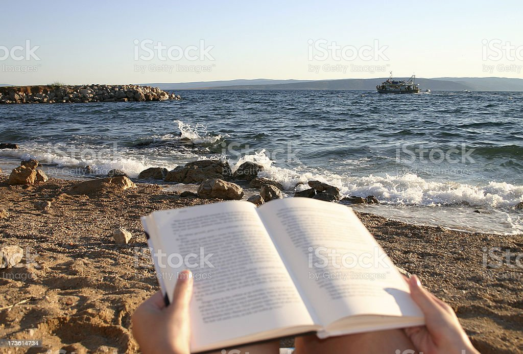 Reading on the beach royalty-free stock photo