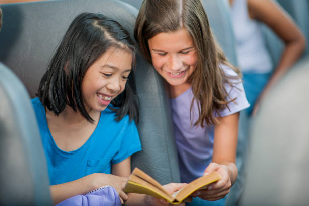 reading on the school bus - two students together asian foto e immagini stock
