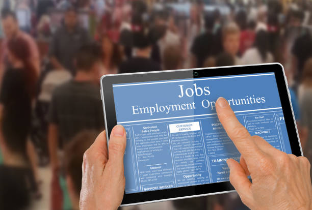 Reading online job ads on a computer tablet stock photo