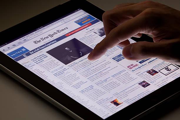 reading online-zeitung auf dem ipad - new york times stock-fotos und bilder