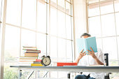 asian woman reading book on desktop in workplace near window