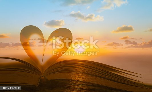 Heart shape from book against peaceful sunset. Multiple exposure.