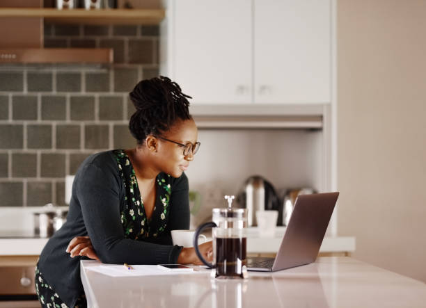 Reading some important emails in kitchen stock photo