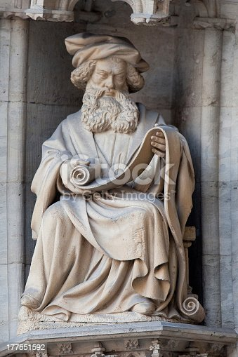 Statue of a reading wise man on the facade of the Brussels Town Hall.