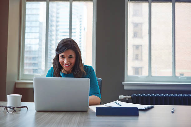 Reading the monthly employee e-newsletter Shot of a businesswoman using a laptop in an office newsletter stock pictures, royalty-free photos & images