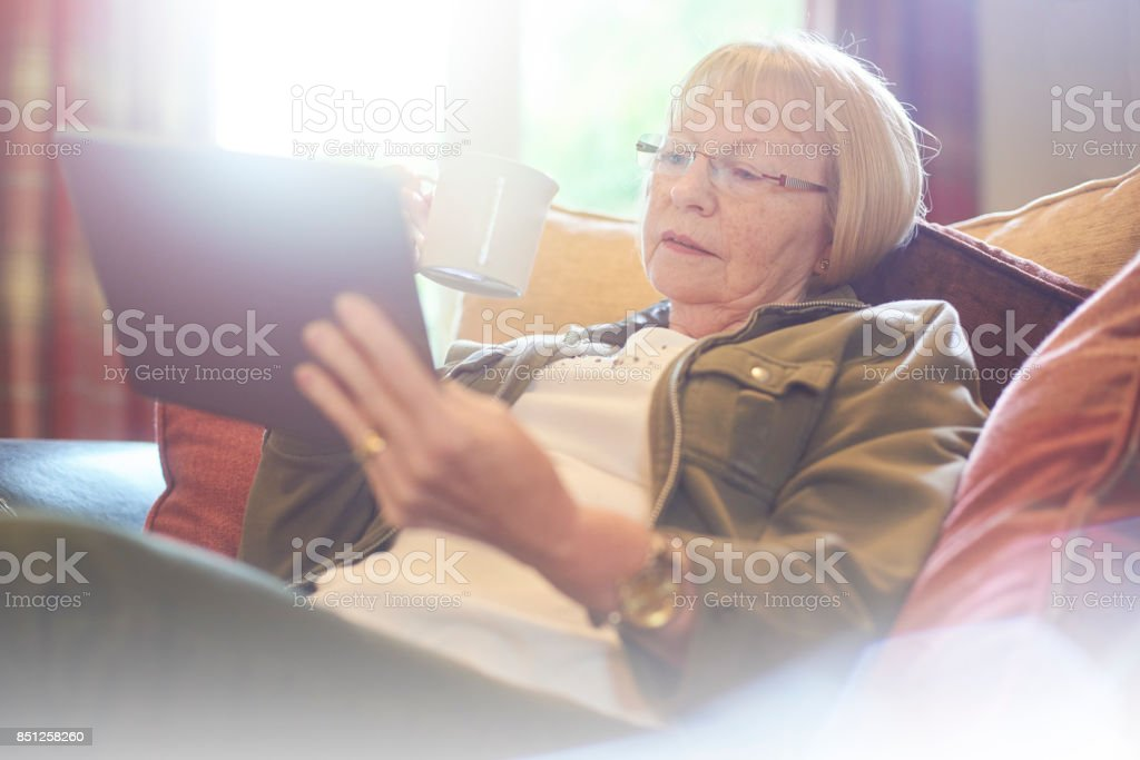 reading the news on digital tablet stock photo