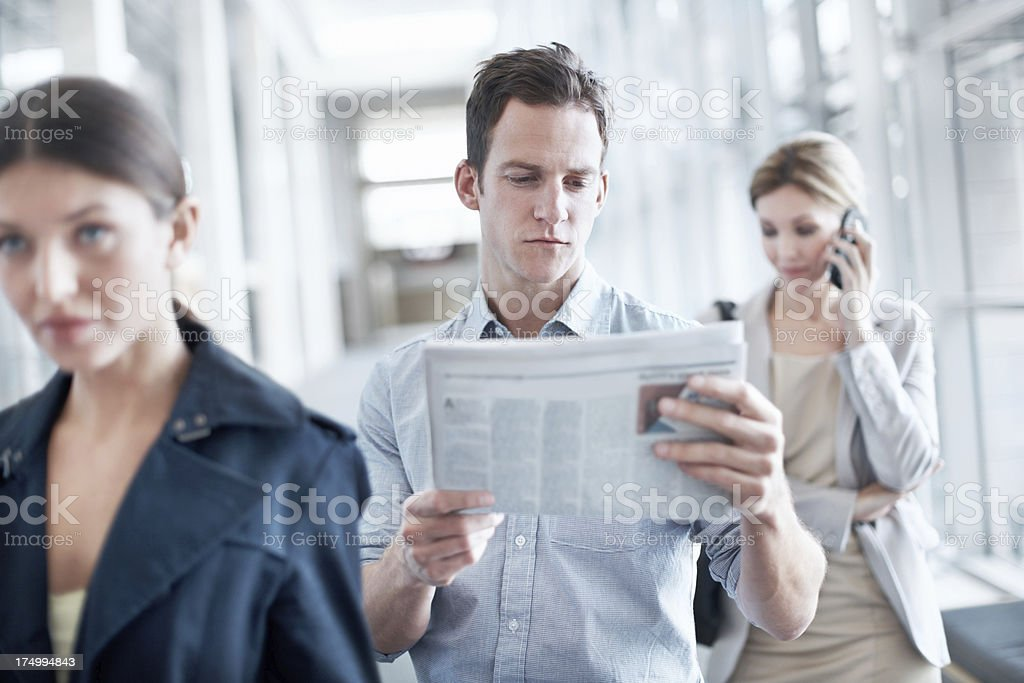 Reading the newspaper while he waits royalty-free stock photo