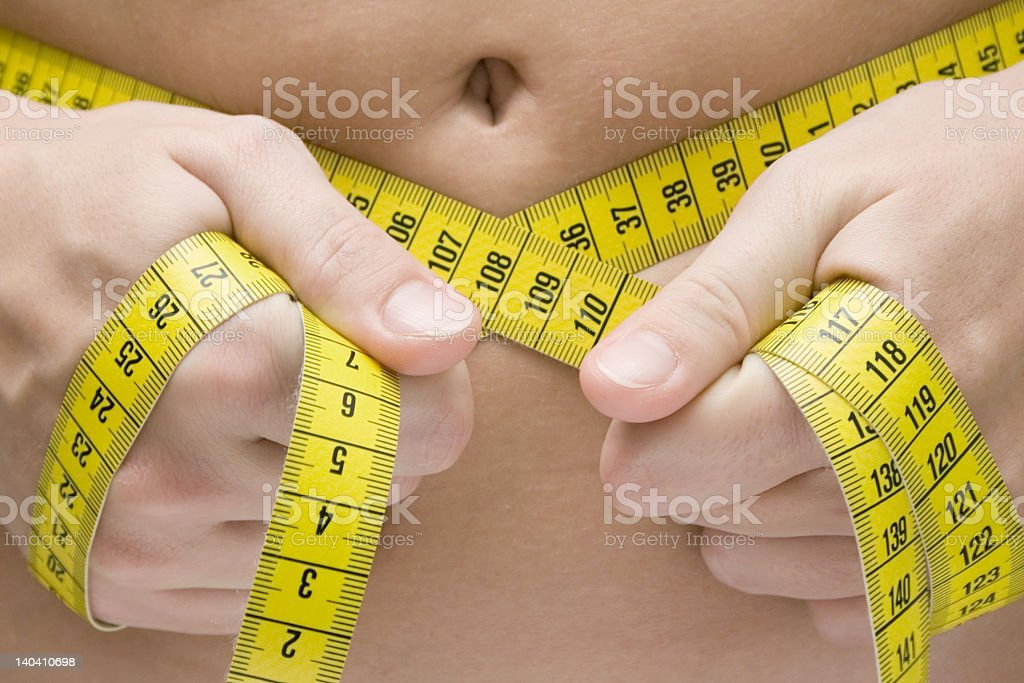 Reading the waistline with a yellow measuring tape stock photo