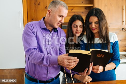 Lovely family in the kitchen reading a Holy bible. Concept for faith, hope and spirituality.