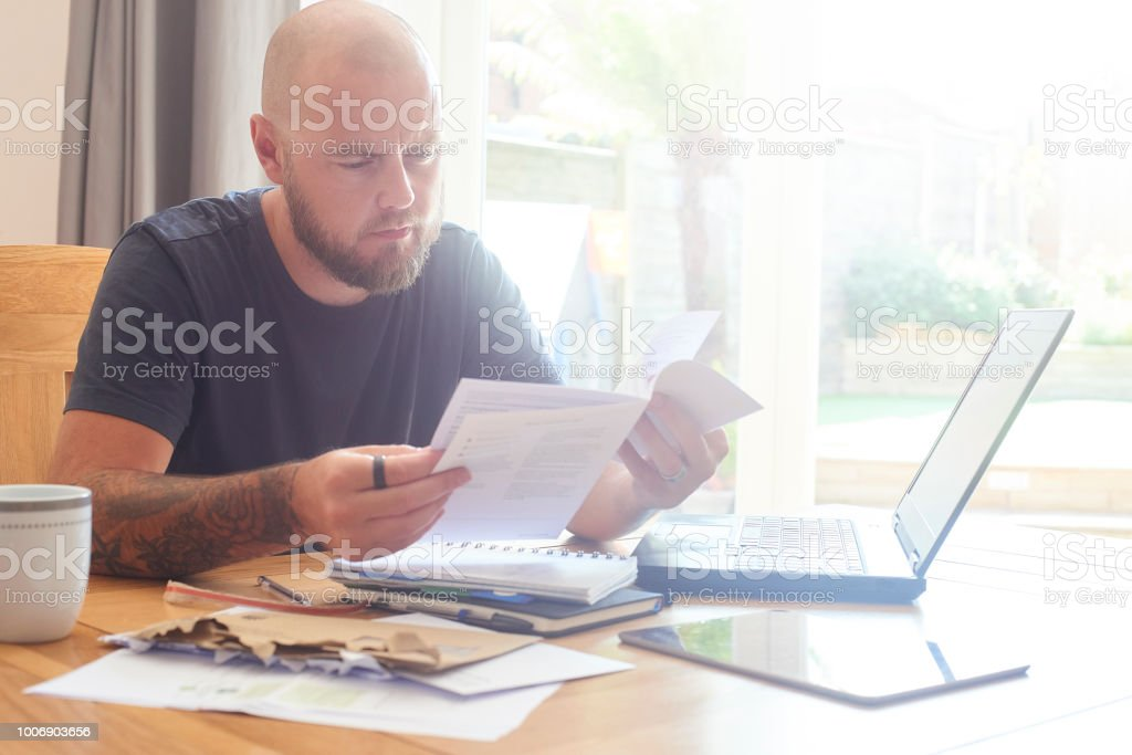Man sat at dining room table working from home or sorting out home...