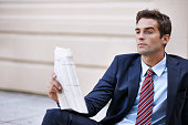 Shot of a handsome businessman reading the stock pages outsidehttp://195.154.178.81/DATA/shoots/ic_782890.jpg