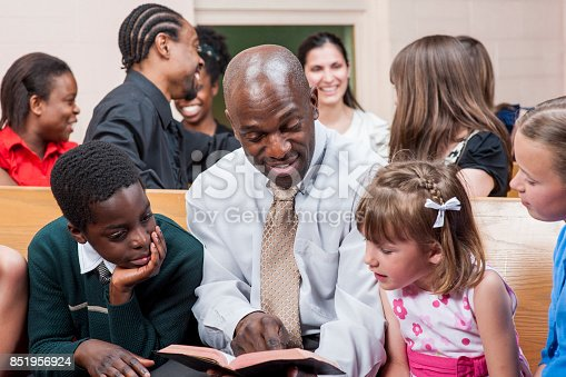A multi-ethnic group of people are indoors in a church. They are wearing clothes suitable for church. A man of African descent is reading a bible to some children.